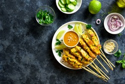 Chicken satay with peanut sauce. Grilled chicken skewers served with peanut dipping sauce. Tasty meal for dinner or party appetizers. Blue stone background with free text space. Top view, flat lay