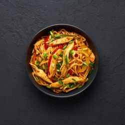 Chicken Schezwan Noodles or Hakka or Chow Mein in black bowl at dark background. Schezwan Noodles is indo-chinese cuisine hot dish with udon noodles, vegetables and chilli sauce or Schezwan sauce