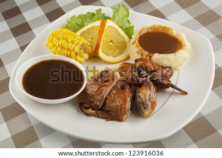 Chicken served with mashed potatos and gravy and a side of corn. With clipping path