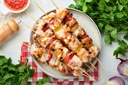 Chicken shish kebab or skewers kebab in a ceramic plate, spices, cilantro herbs and vegetables on white table background. Barbecue Raw ingredients for goulash or shish kebab. Top view. Free copy space