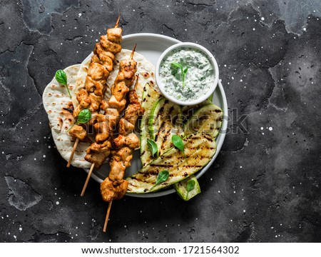 Chicken skewers souvlaki, grilled zucchini, tortillas and tzadziki sauce - delicious greek style lunch on a dark background, top view