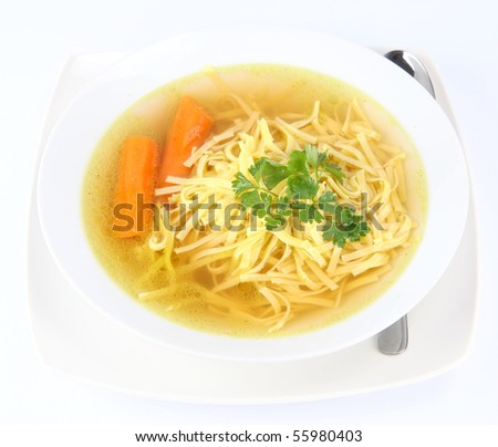 Chicken soup with macaroni and carrots decorated with parsley on a plate with a spoon