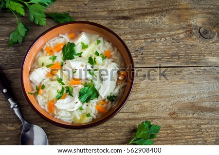 Chicken soup with noodles and vegetables in bowl over rustic wooden background - homemade healthy meal