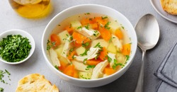 Chicken soup with vegetables in white bowl. Grey stone background. Close up.
