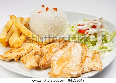 Chicken Steak, served in a dish with rice and  salad.