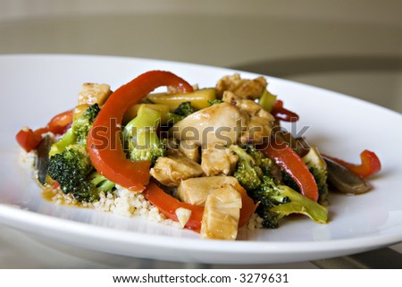 Chicken Stir Fry over Whole Wheat Couscous set on a Glass Table