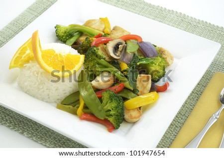 Chicken stir fry with rice on square white plate