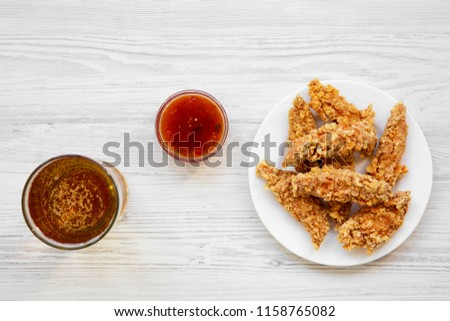 Chicken strips with sauce and cold beer, top view. From above, overhead, flat lay. Closeup.