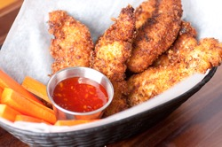 chicken tenders or strips with a spicy chilli sauce and vegetable sticks