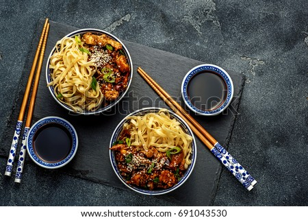 Chicken teriyaki on dark background with balsamic sauce and sesame seeds. Asian food. Noodles. Top view.