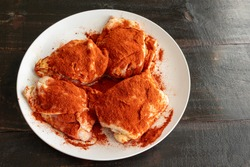 Chicken Thighs Seasoned with Paprika for Chicken Paprikash: Raw chicken thighs sprinkled with Hungarian sweet paprika and pimenton (smoked paprika)
