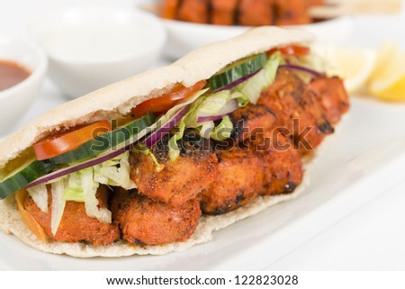 Chicken Tikka Kebab - Tandoori chicken tikka with salad in a pita bread. Served with chilli sauce, yoghurt and lemon wedges on a white background.