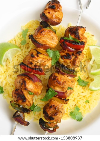 Chicken tikka kebabs with red onions and peppers.
