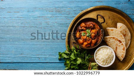 Chicken tikka masala spicy curry meat food Butter chicken with rice and naan bread on blue wooden background copy space