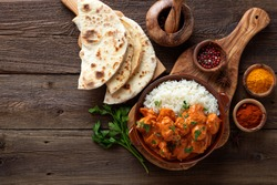 Chicken tikka masala spicy curry meat food in a clay plate with rice and naan bread on wooden background.