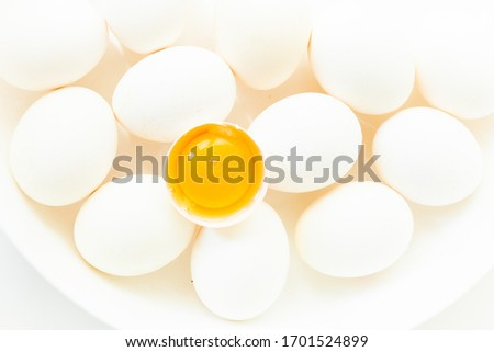 Chicken white eggs on a white background.  Chicken eggs are treated in a white plate and one egg with yolk. Сток-фото ©