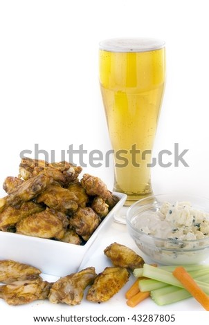 Chicken wings beer and condiments against white
