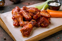 chicken wings in barbecue sauce and with blue cheese sause on dark rustic concrete table