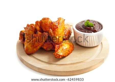Chicken wings on wooden plate isolated over white