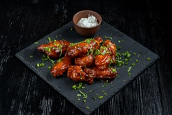 Chicken Wings with tomato barbecue sauce. In a small bowl of horseradish. Diagonal view.