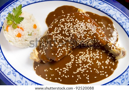 Chicken with mole mexican dish. With mole sauce which is a combination of chili and chocolate and seasoned with sesame seeds. With white vegetable rice on the side.