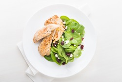 Chicken with spinach salad on white wooden background top view. Healthy food.