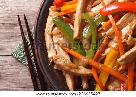 chicken with vegetables macro and chopsticks on the wooden table. horizontal view from above