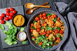 Chickpea and chicken curry of boneless chicken thighs with cherry tomatoes and baby spinach on a frying pan on a black wooden background with ingredients on a table, top view, close-up