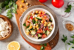Chickpea salad with tomatoes, cucumber, feta cheese, parsley, onions and lemon in a plate on a gray background top view, selective focus. Healthy vegetarian food, oriental and Mediterranean cuisine.