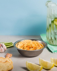 chickpeas dip with paprika bread  and vegetables and cucumber water in a lightblue background