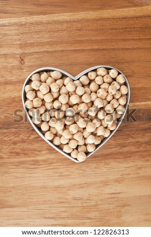 Chickpeas on a heart shaped bowl against wooden background