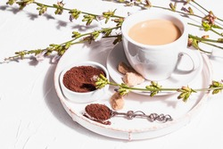 Chicory coffee with fresh flowers and powder. Natural caffeine-free drink in a white cup. Alternative replacement for coffee, caffeine. White plaster background, copy space