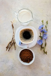Chicory drink with milk in a white Cup with the concentrate from the root and flowers on a light background. Healthy herbal drink, coffee substitute, diabetic coffee with chicory.