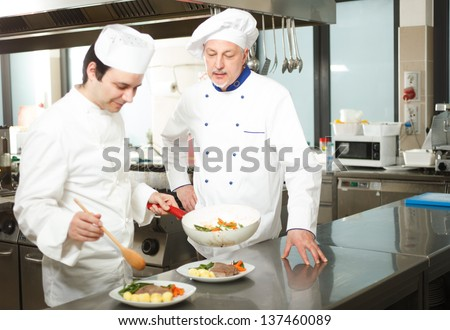 Chief chef watching his assistant garnishing a dish