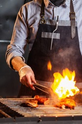 Chief cook is preparing meat at open fire grill at kitchen background. Vertical image.