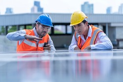 Chief electrical engineer inspects the installation of solar cells on the roof, using solar energy to generate electricity, concept of using renewable energy.