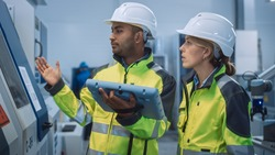 Chief Engineer and Project Manager Wearing Safety Vests and Hard Hats, Use Digital Tablet Controller in Modern Factory, Talking, Optimizing CNC Machinery, Increasing Production Line Efficiency