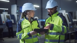 Chief Engineer and Project Manager Wearing Safety Vests and Hard Hats, Use Digital Tablet Computer in Modern Factory, Talking, Optimizing Production Line. Industrial Facility with CNC Machinery