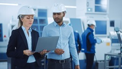 Chief Engineer and Project Manager Wearing Safety Vests and Hard Hats, Use Laptop in Modern Factory, Talking, Optimizing Production Line. Industrial Facility: Professionals Working on Machinery