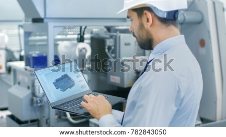 Chief Engineer in the Hard Hat Holds Laptop with 3D Component Model on it's Screen. In the Background Modern Factory Equipment.