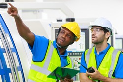 Chief manufacturer guiding worker guy to correct the production process, the Hispanic and black guy colleague collaborating at the factory.