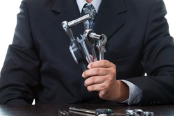 Chief mechanical engineer holding many tools and measurement equipment in his hands