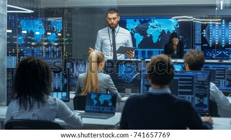 Chief Project Engineer Holds Briefing for a Team of Scientists that are Building Machine Learning System. Displays Show Working Model of Neural Network.
