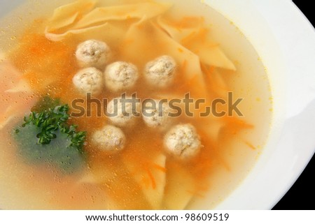 chiken noodle soup with noisettes in a white bowl closeup on a white background