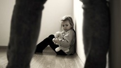 Child abuse concept. Mistreated little girl seating on the floor and scared of adult.
