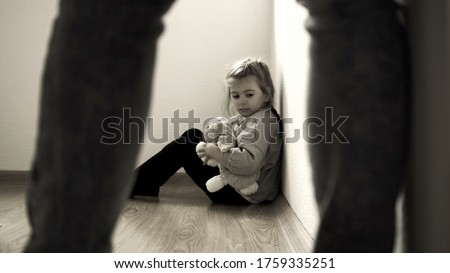Child abuse concept. Mistreated little girl seating on the floor and scared of adult. Stock photo ©