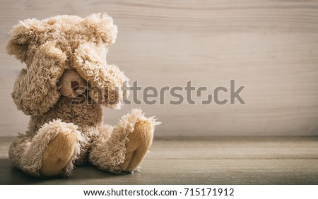 Child abuse concept. Teddy bear covering eyes in an empty room, front view, copy space