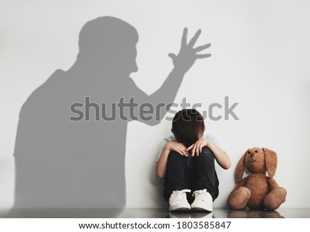Child abuse. Father yelling at his son. Shadow of man on wall Stock photo ©