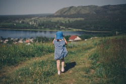 child against the background of wild nature. Russian mountains, plains, fields. the girl in the tall grass and looks into the distance
