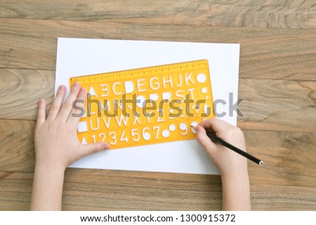 Child alphabet ruler with writes lettering on wood table